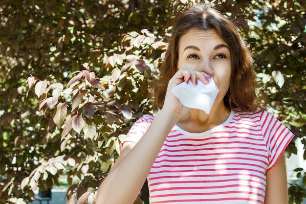 Frau mit mit allergiesymptomschlagnase im park