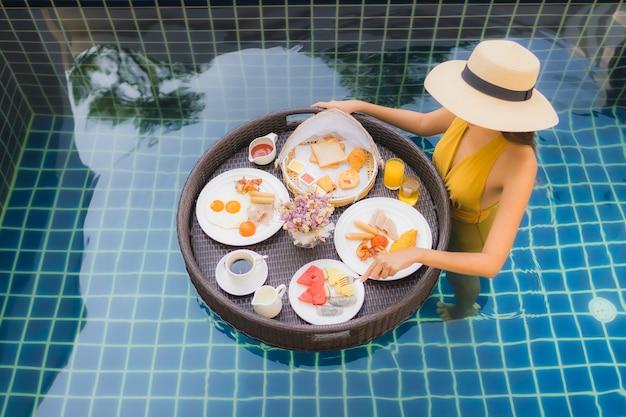 Frau mit mit dem frühstück, das um swimmingpool schwimmt