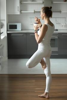 Frau mit mittagessen in baum pose