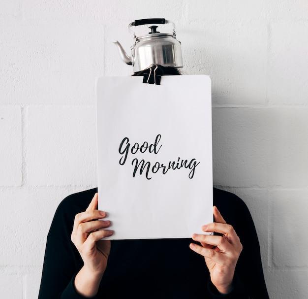 Frau mit mitteilung des kessels oben und des gutenmorgens auf papierholding vor gesicht gegen weiße wand