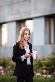 Frau mit mittlerem schuss des kaffees und des telefons