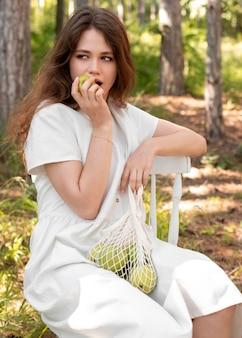 Frau mit mittlerem schuss, die apfel isst