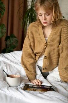 Frau mit mittlerem schuss, die auf tablet schaut