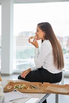 Frau mit mittlerem schuss, die bei der arbeit pizza isst