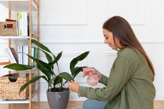 Frau mit mittlerem schuss, die ein blatt gießt