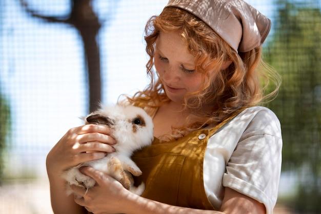 Frau mit mittlerem schuss, die ein kaninchen hält