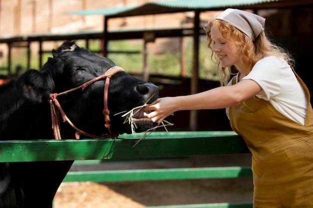 Frau mit mittlerem schuss, die ein tier füttert