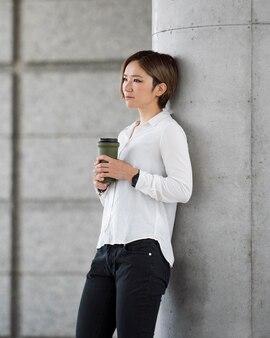 Frau mit mittlerem schuss, die eine kaffeeflasche hält