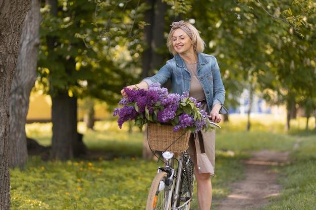 Frau mit mittlerem schuss, die fahrrad fährt