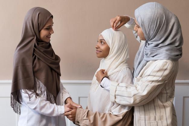 Frau mit mittlerem schuss, die hijab arrangiert