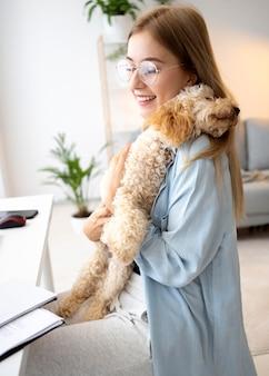 Frau mit mittlerem schuss, die hund hält