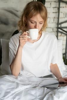 Frau mit mittlerem schuss, die kaffee trinkt