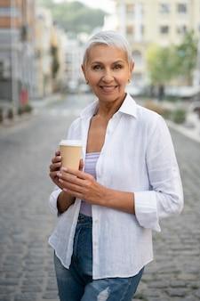 Frau mit mittlerem schuss, die kaffeetasse hält