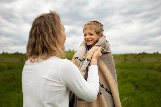 Frau mit mittlerem schuss, die kind hält