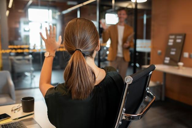 Frau mit mittlerem schuss, die kollegin mit den händen winkt