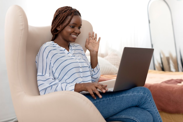Frau mit mittlerem schuss, die laptop hält