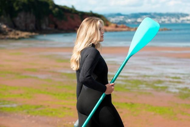 Frau mit mittlerem schuss, die paddel hält