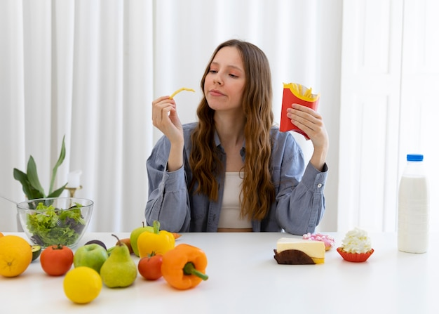 Frau mit mittlerem schuss, die pommes hält