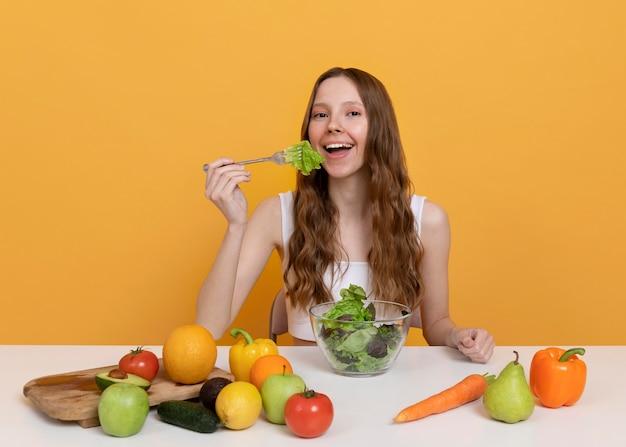 Frau mit mittlerem schuss, die salat isst