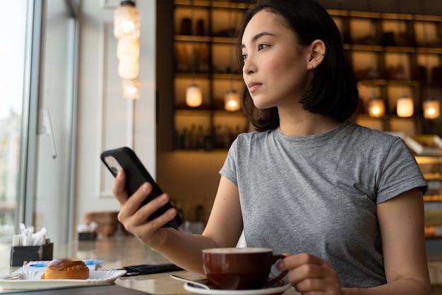 Frau mit mittlerem schuss, die smartphone hält