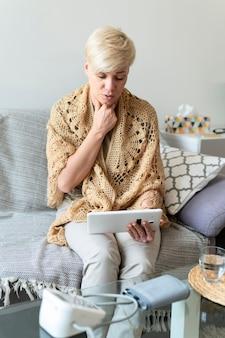 Frau mit mittlerem schuss, die tablette hält