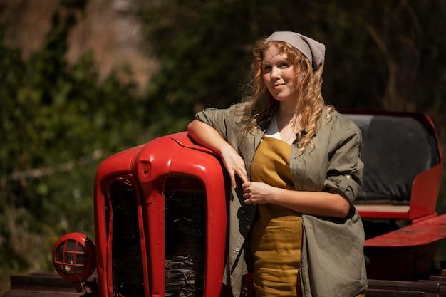 Frau mit mittlerem schuss in der nähe einer landmaschine