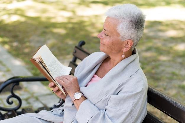 Frau mit mittlerem schuss liest auf bank
