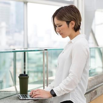 Frau mit mittlerem schuss tippt auf laptop