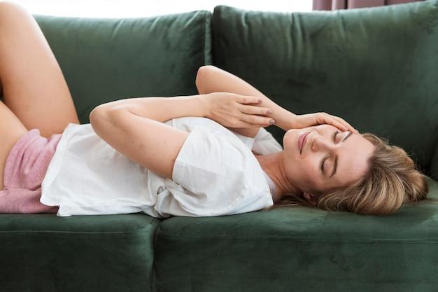 Frau mit mittlerer ansicht, die auf der couch sitzt