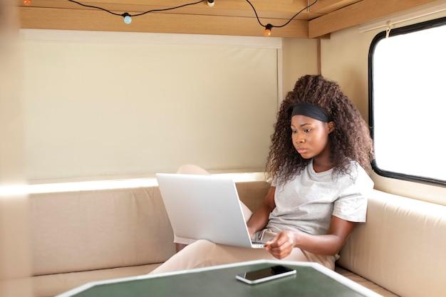 Frau mit mittlerer aufnahme arbeitet am laptop