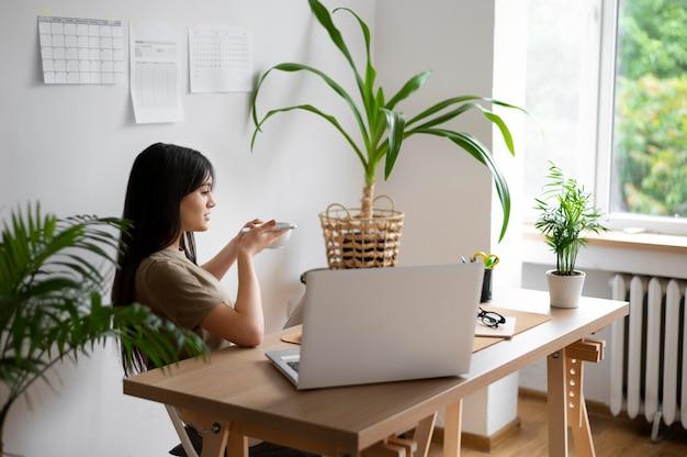 Frau mit mittlerer aufnahme, die am schreibtisch sitzt