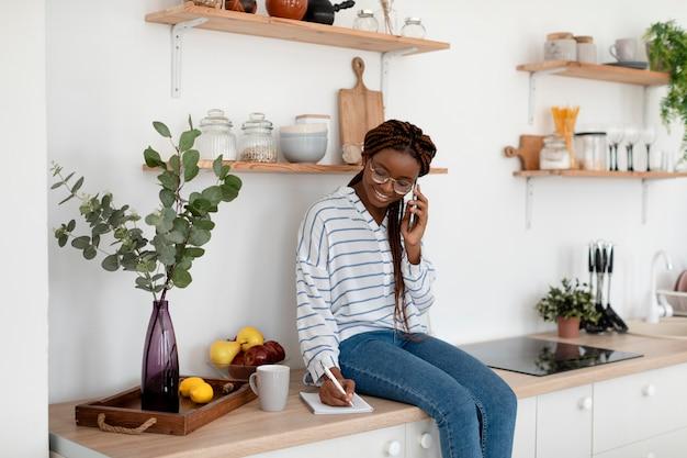 Frau mit mittlerer aufnahme, die am telefon telefoniert