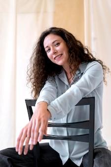 Frau mit mittlerer aufnahme, die auf stuhl sitzt