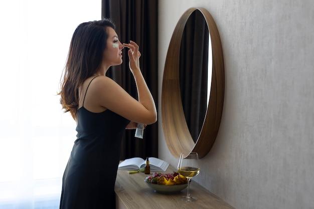 Frau mit mittlerer aufnahme, die in den spiegel schaut