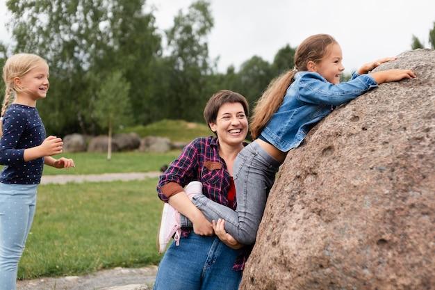 Frau mit mittlerer aufnahme, die mit kindern spielt