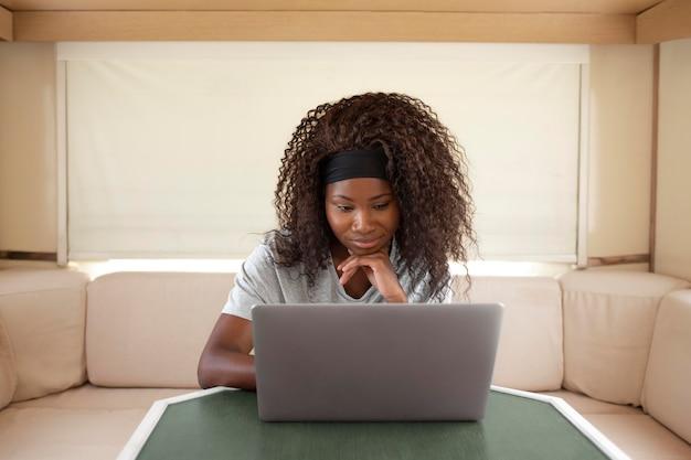 Frau mit mittlerer aufnahme, die mit laptop arbeitet