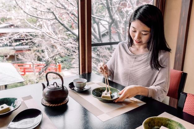 Frau mit mittlerer aufnahme, die mit stäbchen isst