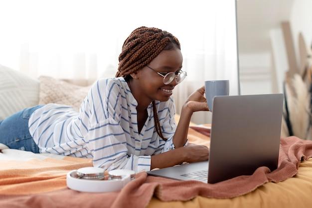 Frau mit mittlerer aufnahme, die sich mit laptop entspannt