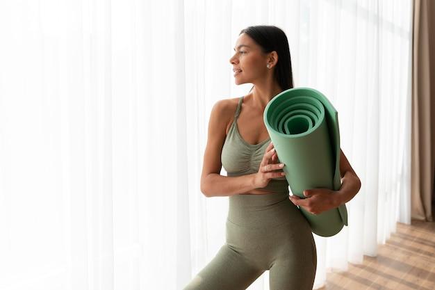 Frau mit mittlerer aufnahme, die yogamatte hält