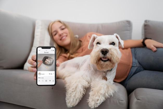Frau mit mittlerer aufnahme und hund mit telefon