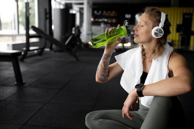 Frau mit mittlerer schussweite, die wasser trinkt
