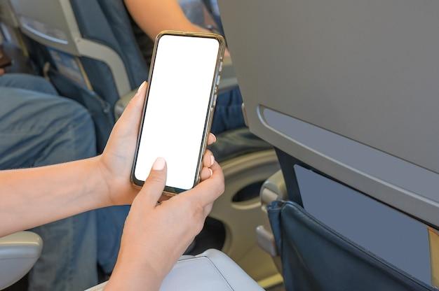 Frau mit mock-up-handy beim sitzen im flugzeug. frau mit smartphone im flugzeug während des fluges. modellbild der hände einer frau, die ein schwarzes smartphone mit leerem desktop-bildschirm halten