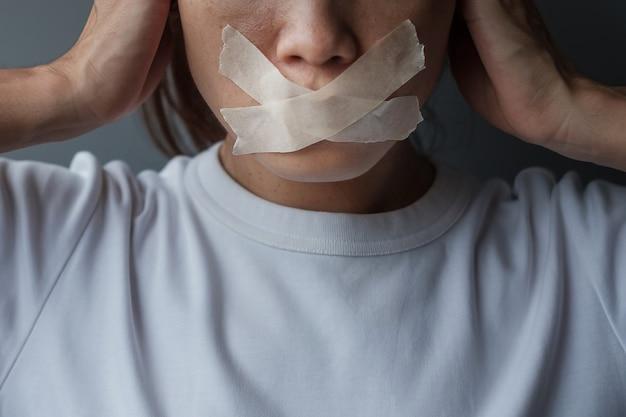 Frau mit mund mit klebeband versiegelt. meinungsfreiheit, pressefreiheit, menschenrechte, protestdiktatur, demokratie, freiheit, gleichheit und brüderlichkeitskonzepte