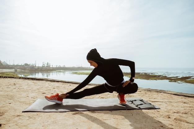 Frau mit muslimischer sportabnutzung dehnung