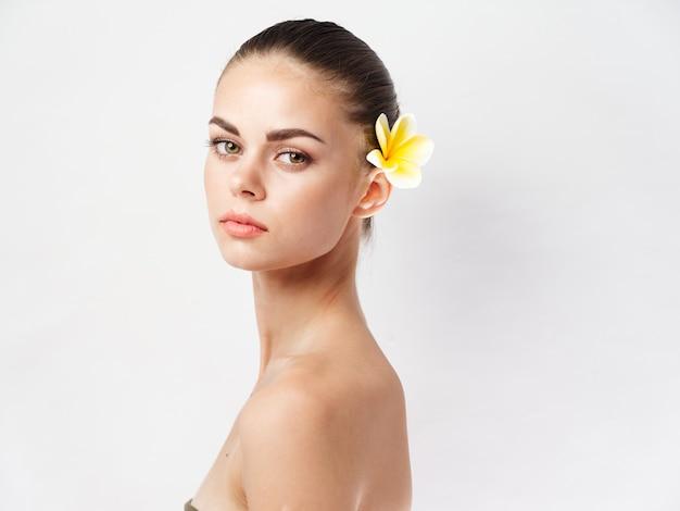 Frau mit nackten schultern gesicht make-up gelbe blume attraktiven look