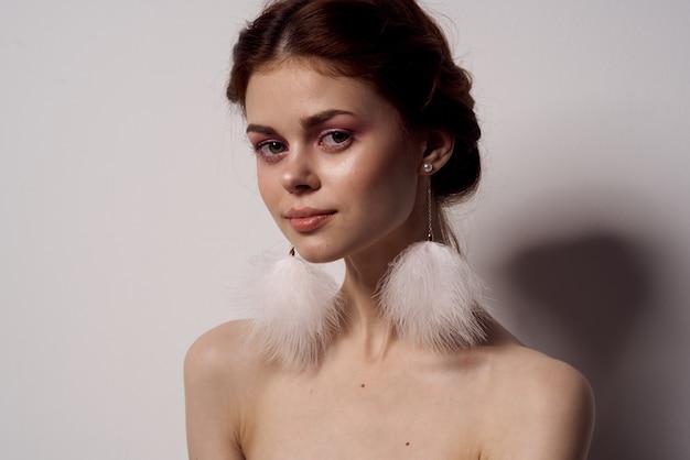 Frau mit nackten schultern hellem make-up flauschige ohrringe mode hellen hintergrund