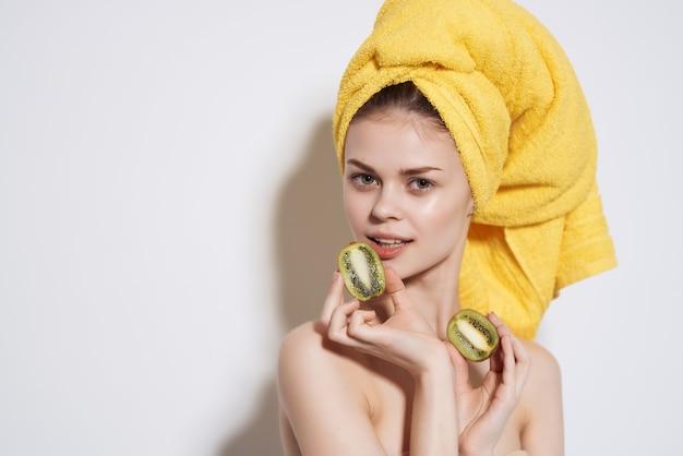 Frau mit nackten schultern kiwi in den händen klare haut vitamine früchte