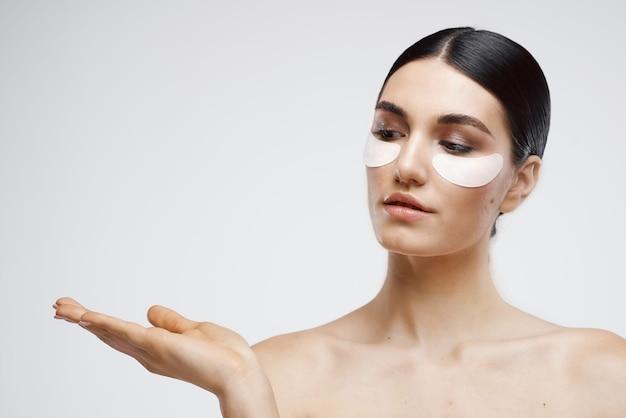 Frau mit nackten schultern patches in der nähe von augenkosmetik