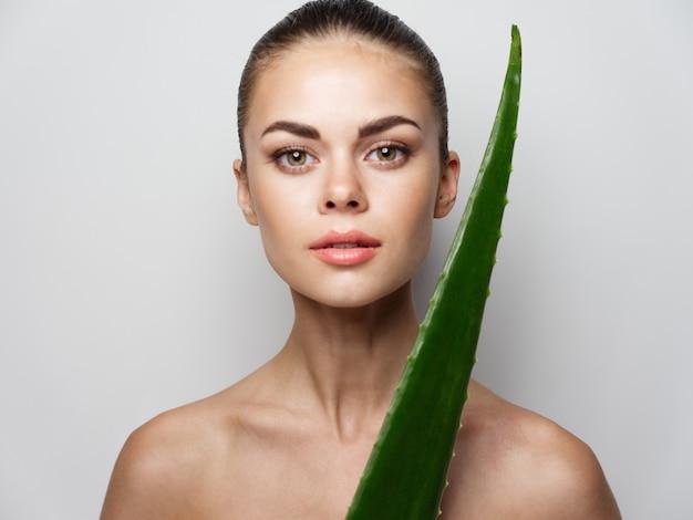 Frau mit nackten schultern saubere hautkosmetik und grünes aloe-blatt
