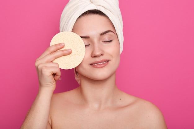 Frau mit nackten schultern, schwamm zum auftragen der make-up-grundlage haltend, frau, die im badezimmer mit steht